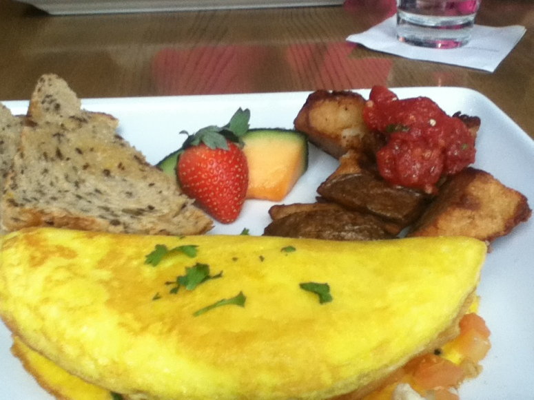 Spinach and feta omelet with potatoes and diced Roma tomatoes.