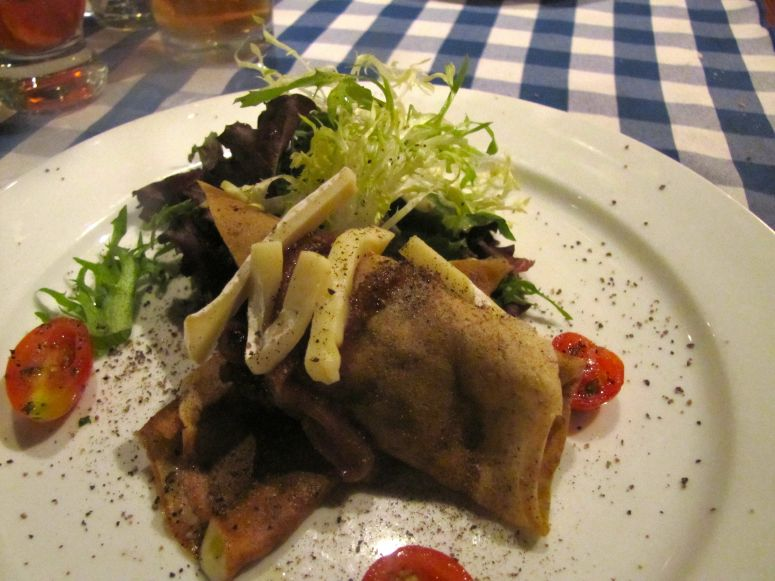 Buckwheat crepe with caramelized onions, mixed green leaf vegetables and Brie