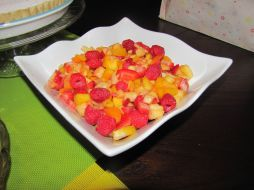 Chopped fruit salad featuring, mangoes, fresh peaches, apricots, pineapple, strawberries, rasberries with a honey, cinnamon lime dressing.